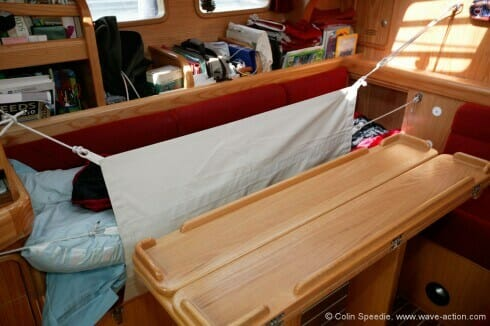 By specifying a right angle at the back of the port hand settee, together with a trotter box to put your feet in, we were able to create a full length berth for tall crew members. The lee cloth is high enough to keep the inhabitant of the berth safe in all conditions, and can be double fastened for extra security.