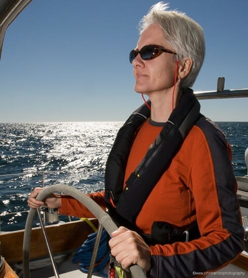"""Phyllis Nickel at the helm of """"Morgan's Cloud"""" during a sunny windy afternoon sail off Jonesport, Maine."""