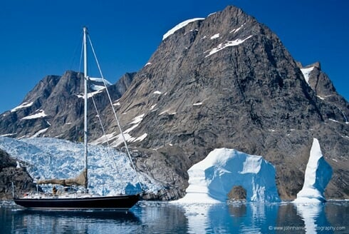 """""""Morgan's Cloud"""", a McCurdy and Rhodes 56' cutter, seen beside an arch berg with glacier and mountain behind, a typical East Greenland scene. The icecap reaches down to the sea in numerous glaciers and there are a floating profusion of bergs and smaller pieces of ice to be carefully avoided."""