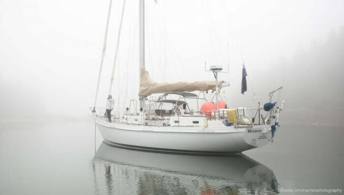 """Phyllis gets """"Morgan's Cloud"""" ready to get underway. There's a bit of visibility in the snug cove, but outside it will be pea-soup."""